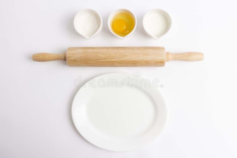 Αυγό, αλεύρι, γάλα, ξύλινη κυλώντας καρφίτσα και άσπρο πιάτο στο άσπρο υπόβαθρο στοκ εικόνες