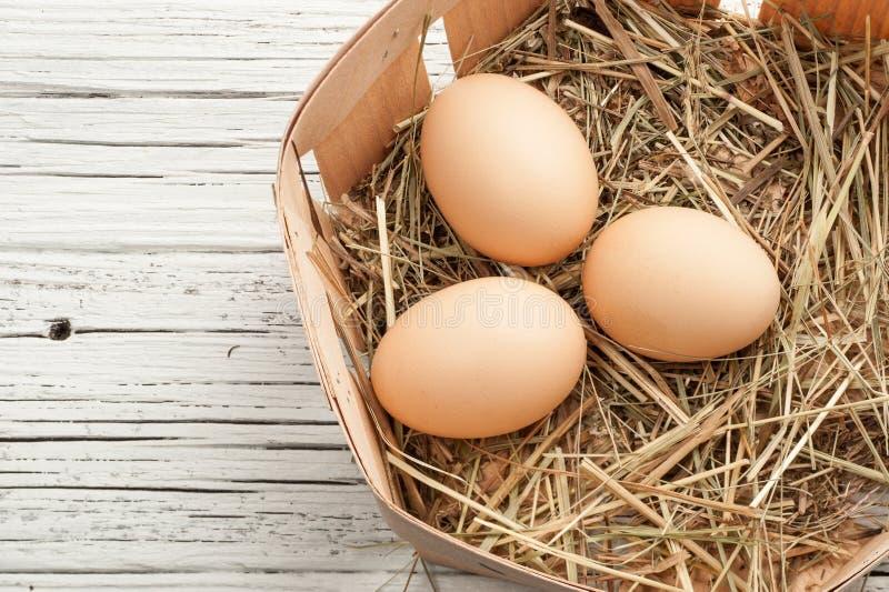 Αυγό κοτόπουλου σε μια φωλιά αχύρου στο άσπρο παλαιό ξύλινο υπόβαθρο στοκ φωτογραφία με δικαίωμα ελεύθερης χρήσης