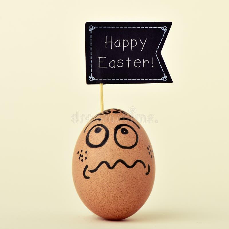Αυγό με ένα αστείο πρόσωπο με μια πινακίδα με το ευτυχές easte κειμένων στοκ φωτογραφία με δικαίωμα ελεύθερης χρήσης