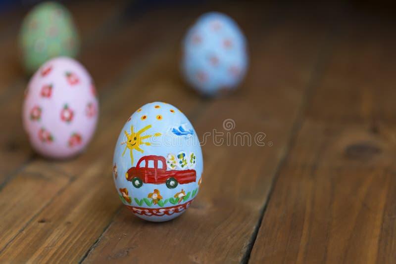 Αυγό Πάσχας με ένα αυτοκίνητο σε έναν ξύλινο πίνακα στοκ εικόνα