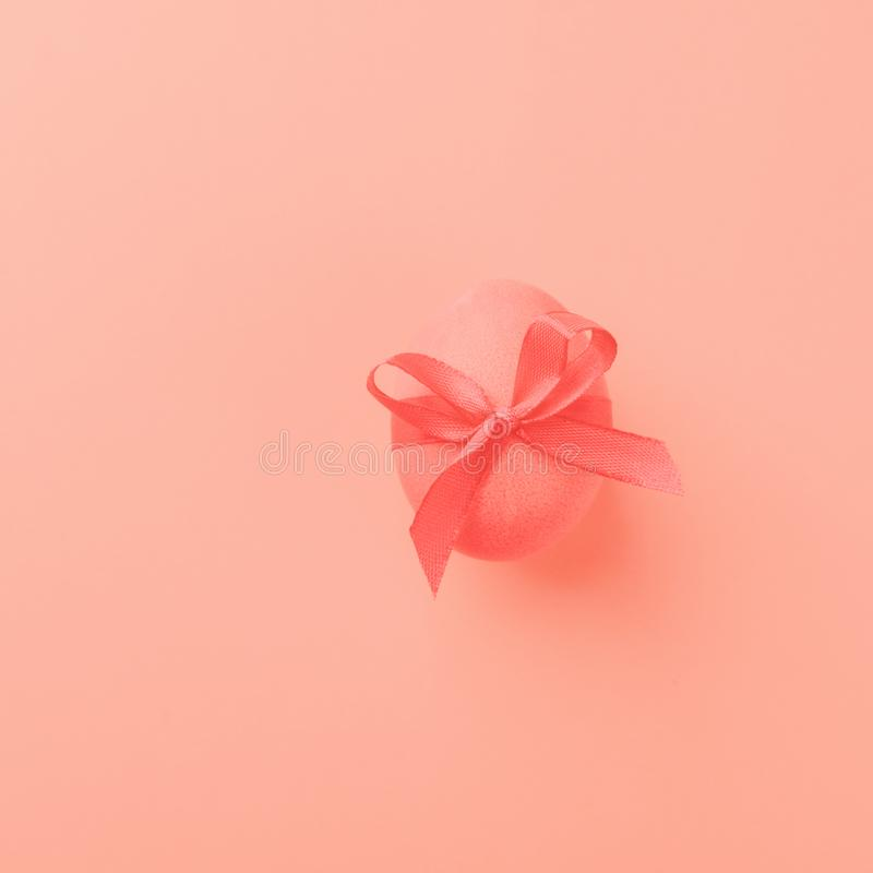 Αυγό Πάσχας σε ένα καθιερώνον τη μόδα υπόβαθρο χρώματος κοραλλιών Εορταστική έννοια μινιμαλισμός διάστημα αντιγράφων στοκ εικόνα