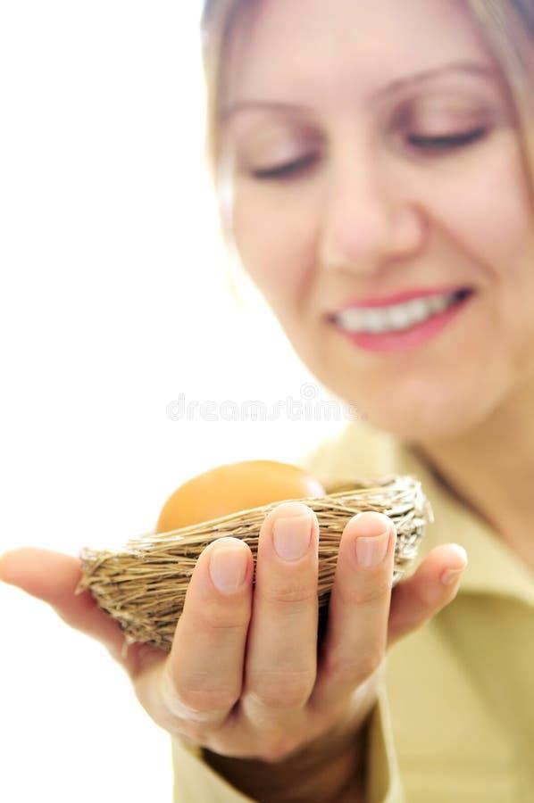 αυγό που κρατά την ώριμη γυ&nu στοκ εικόνα