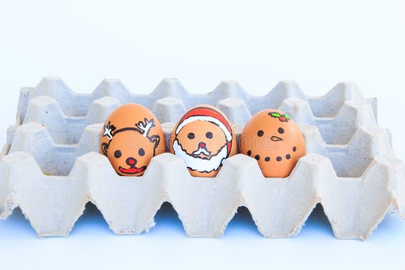 Αυγό Χριστουγέννων με τα πρόσωπα που σύρονται που τακτοποιούνται στο χαρτοκιβώτιο στοκ φωτογραφίες