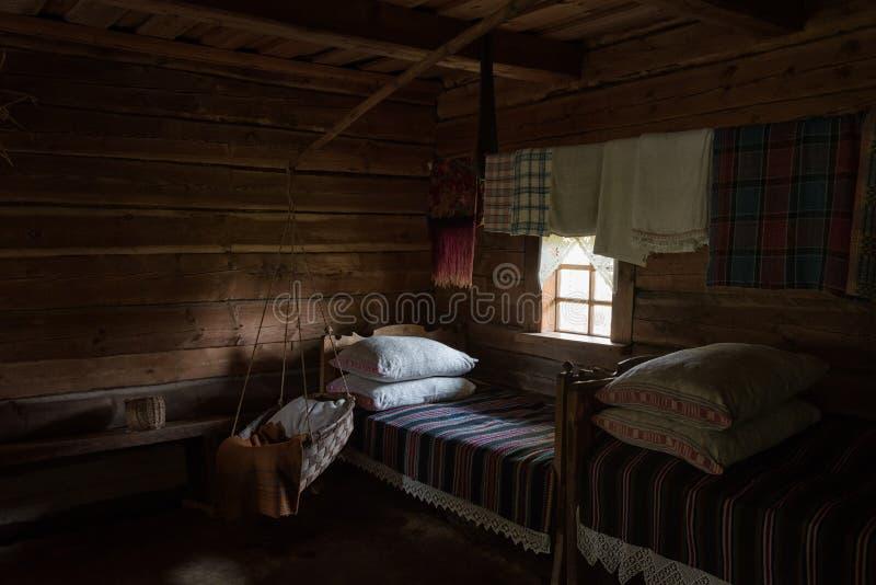 Αυθεντική κρεβατοκάμαρα με το εσωτερικό ξύλινο σπίτι Λιθουανία λίκνων στοκ φωτογραφίες