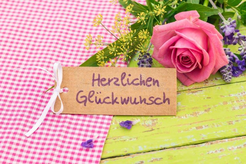 Αυξήθηκε ανθοδέσμη λουλουδιών με τη ευχετήρια κάρτα και το γερμανικό κείμενο, Herzlichen Glueckwunsch, συγχαρητήρια μέσων στοκ εικόνες