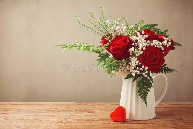 Αυξήθηκε ανθοδέσμη λουλουδιών και κιβώτιο μορφής καρδιών στον ξύλινο πίνακα με το διάστημα αντιγράφων στοκ εικόνα με δικαίωμα ελεύθερης χρήσης