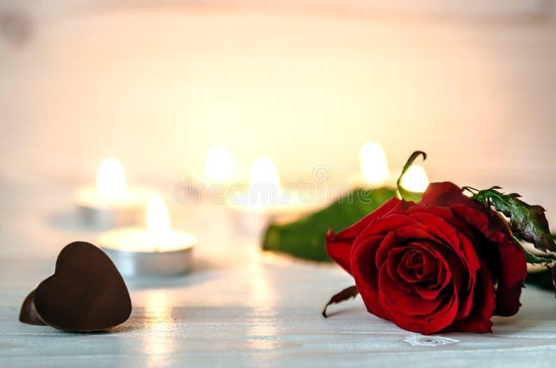 Αυξήθηκε στο λευκό μια ξύλινη επιφάνεια Στο υπόβαθρο είναι αναμμένα μικρά κεριά Δίπλα στο λουλούδι είναι δύο σοκολάτες στο sha στοκ εικόνες
