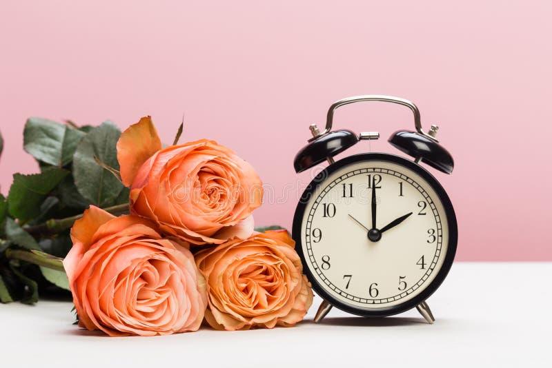 Αυξήθηκε τριαντάφυλλα και ρολόι στο ρόδινο υπόβαθρο, αποταμίευση φωτός της ημέρας στοκ φωτογραφία με δικαίωμα ελεύθερης χρήσης