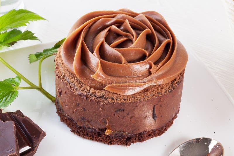 Αυξήθηκε mousse σοκολάτας κέικ σε μια όμορφη κρέμα πιάτων στοκ φωτογραφία
