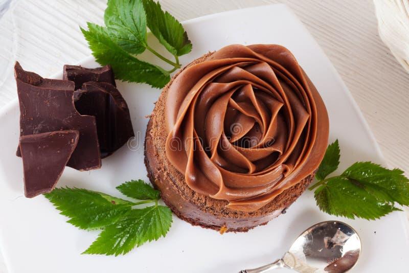 Αυξήθηκε mousse σοκολάτας κέικ σε μια όμορφη κρέμα πιάτων στοκ εικόνες