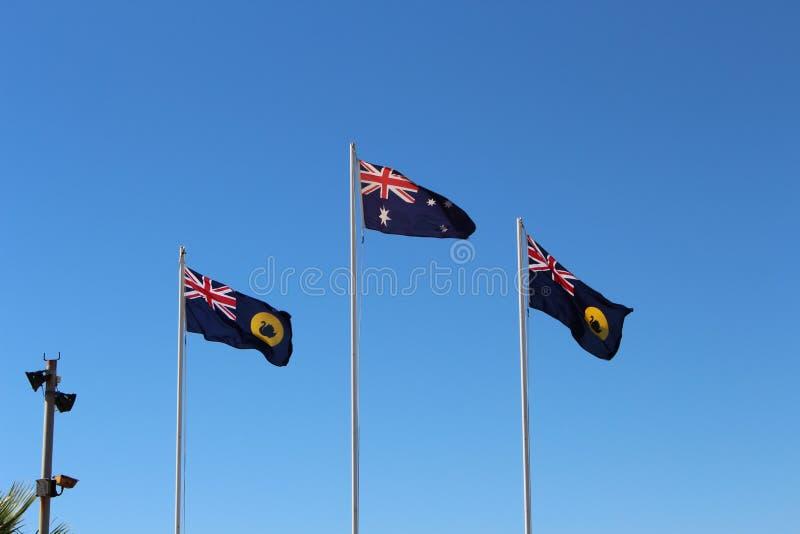 Αυστραλιανές και δυτικές αυστραλιανές σημαίες που πετούν ενάντια στο μπλε ουρανό στοκ εικόνες