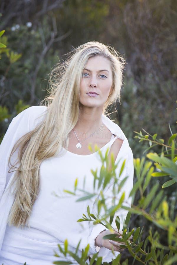 Αυστραλός με τα μακριά ξανθά μαλλιά σχετικά με το δέντρο στοκ φωτογραφία