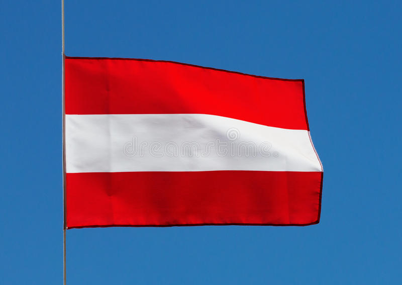 Αυστριακή σημαία στον αέρα ενάντια στον ουρανό στοκ εικόνα