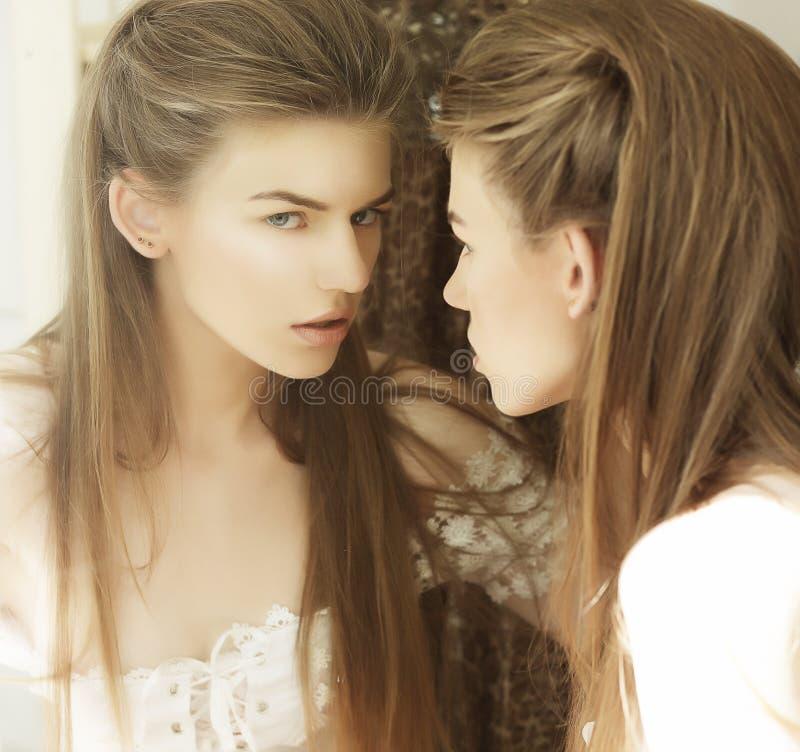Αυταπάτη. Εικόνα της όμορφης γυναίκας μπροστά από έναν καθρέφτη στοκ εικόνα