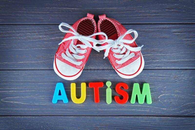 ΑΥΤΙΣΜΟΣ λέξης με τα παπούτσια παιδιών στο υπόβαθρο στοκ φωτογραφίες με δικαίωμα ελεύθερης χρήσης