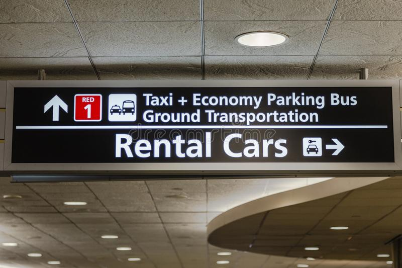 Αυτοκίνητα ενοικίου αερολιμένων, χώρος στάθμευσης και αλεσμένο σημάδι μεταφορών στοκ φωτογραφία με δικαίωμα ελεύθερης χρήσης