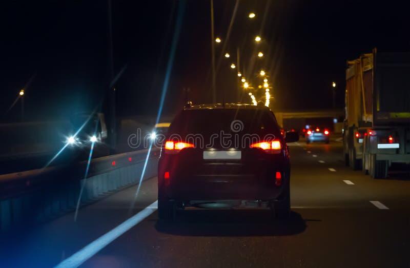 Αυτοκίνητα με τα φω'τα στην κίνηση στον ευρύ δρόμο τη νύχτα στοκ εικόνα
