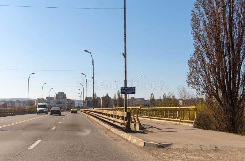 Αυτοκίνητα που διασχίζουν τη γέφυρα πέρα από τον ποταμό Bistrita στην είσοδο στην πόλη Bacau στη Ρουμανία στοκ φωτογραφία