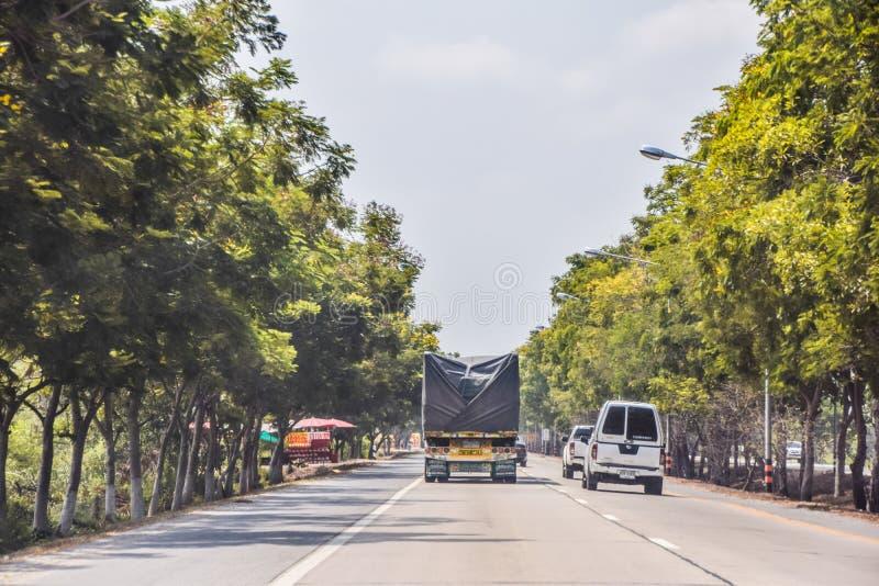 Αυτοκίνητα που τρέχουν προσπερνώντας τα φορτηγά στους αγροτικούς δρόμους στη μέση των δέντρων και τον καυτό καιρό στην Ταϊλάνδη - στοκ φωτογραφία με δικαίωμα ελεύθερης χρήσης