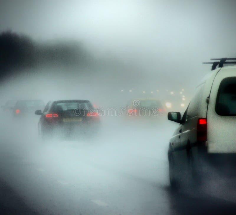 Αυτοκίνητα σε έναν δρόμο στη δυνατή βροχή και την ομίχλη στοκ εικόνα με δικαίωμα ελεύθερης χρήσης