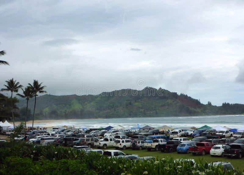Αυτοκίνητα, φορτηγά, και SUV που σταθμεύουν κατά μήκος της παραλίας με τις σκηνές κατά τη διάρκεια του διαγωνισμού κυματωγών στοκ εικόνα