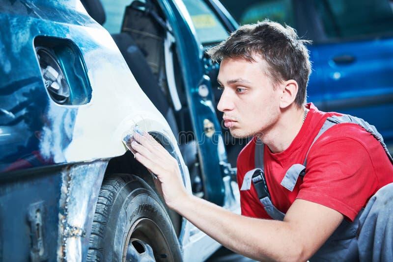 Αυτοκίνητη επισκευή μηχανικό puttying σώμα αυτοκινήτων στοκ φωτογραφία με δικαίωμα ελεύθερης χρήσης