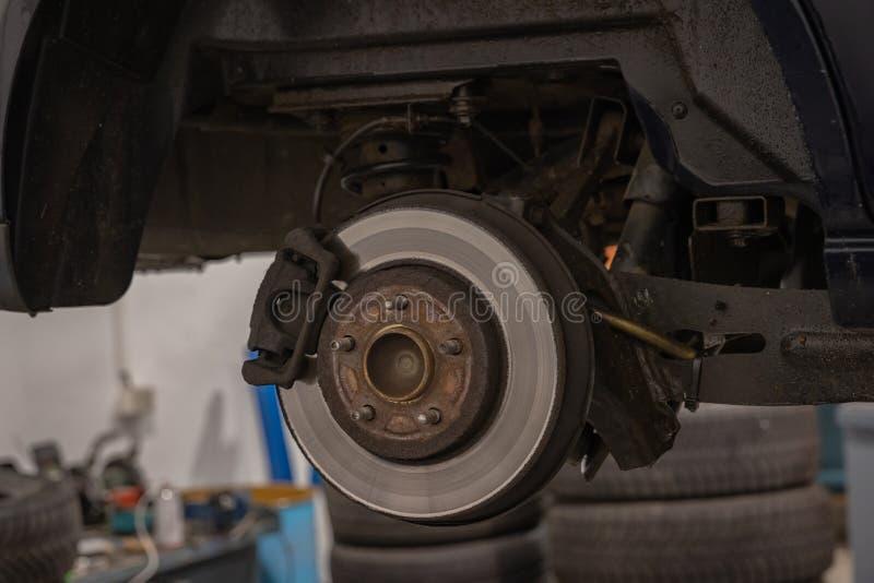 Αυτοκίνητο επισκευής και ελέγχου στο κατάστημα επισκευής Ένας πεπειραμένος τεχνικός επισκευάζει το ελαττωματικό μέρος του αυτοκιν στοκ φωτογραφία