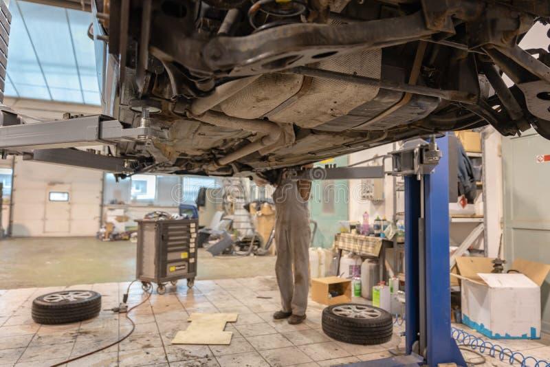 Αυτοκίνητο επισκευής και ελέγχου στο κατάστημα επισκευής Ένας πεπειραμένος τεχνικός επισκευάζει το ελαττωματικό μέρος του αυτοκιν στοκ εικόνα