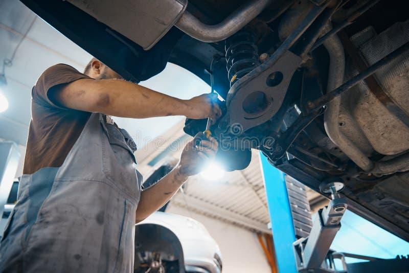 Αυτοκίνητο επισκευής και ελέγχου στο κατάστημα επισκευής Ένας πεπειραμένος τεχνικός επισκευάζει το ελαττωματικό μέρος του αυτοκιν στοκ εικόνα με δικαίωμα ελεύθερης χρήσης