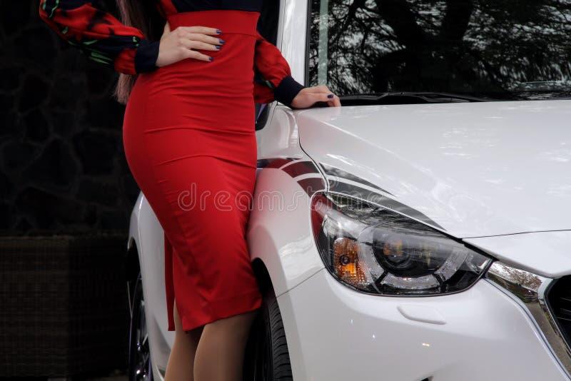Αυτοκίνητο και μόδα Πρότυπο κορίτσι στο κόκκινο φόρεμα κοντά στο νέο άσπρο αυτοκίνητο στοκ εικόνες