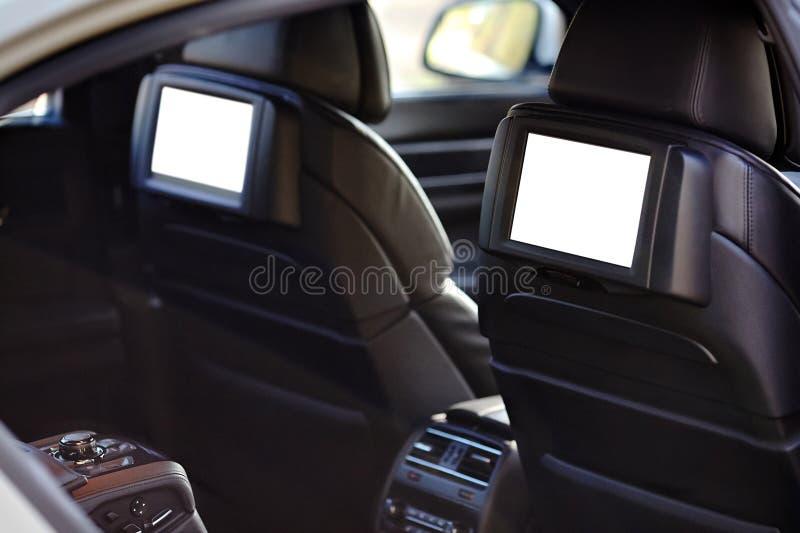 Αυτοκίνητο μέσα headrest στη χλεύη οθονών επάνω Εσωτερικό του σύγχρονου αυτοκινήτου πολυτέλειας γοήτρου Δύο άσπρες επιδείξεις TV  στοκ φωτογραφίες με δικαίωμα ελεύθερης χρήσης
