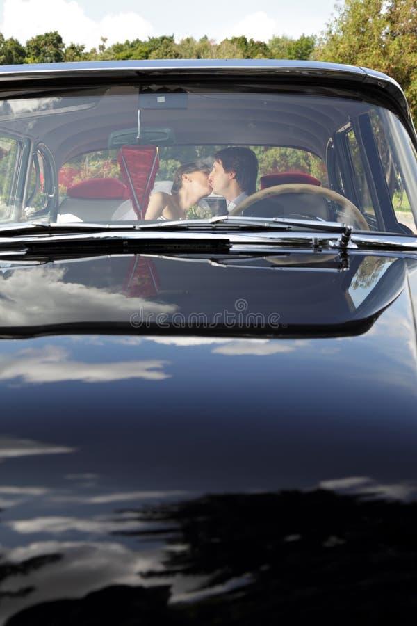 Αυτοκίνητο με το φίλημα της νύφης και του νεόνυμφου στοκ φωτογραφία με δικαίωμα ελεύθερης χρήσης