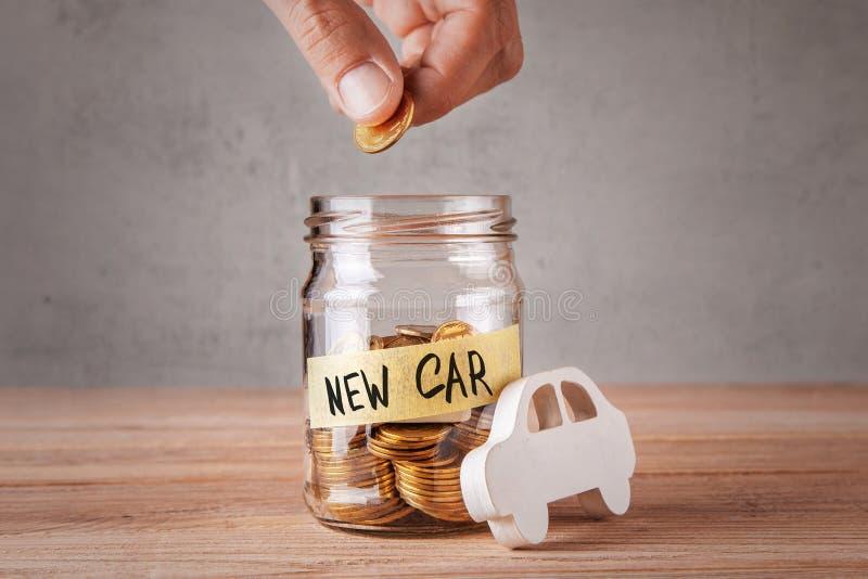 αυτοκίνητο νέο Βάζο γυαλιού με τα νομίσματα και μια επιγραφή του νέου αυτοκινήτου και σύμβολο του αυτοκινήτου στοκ εικόνα