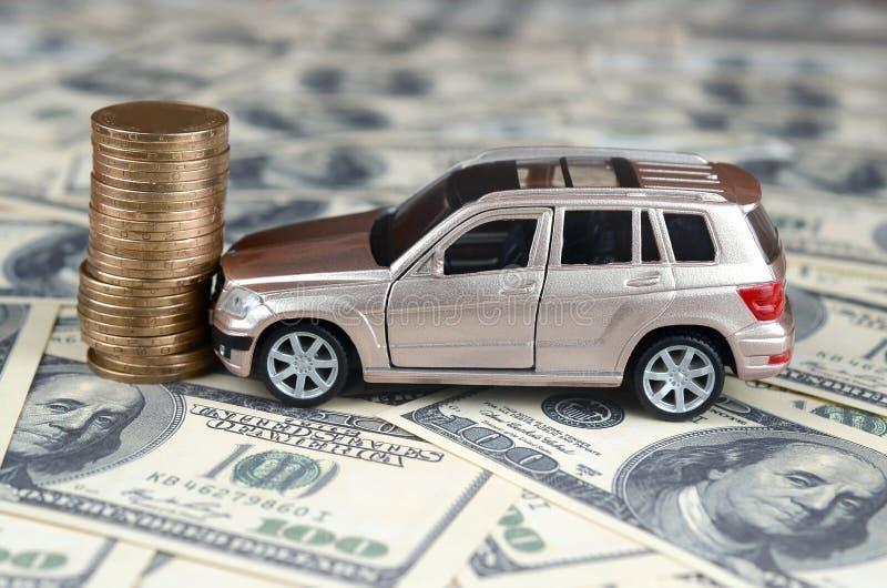 Αυτοκίνητο παιχνιδιών στο ατύχημα σε ένα υπόβαθρο 100 λογαριασμών δολαρίων και το σωρό των χρυσών νομισμάτων στοκ φωτογραφίες