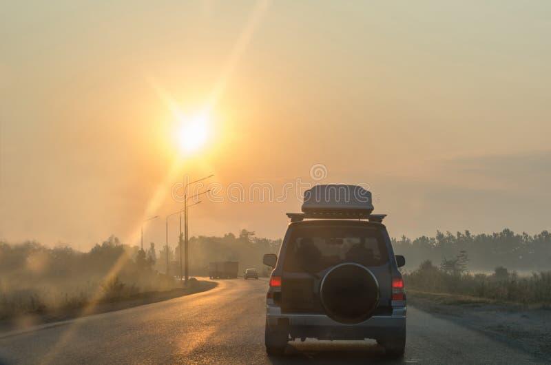 Αυτοκίνητο που κινείται στο δρόμο στην επαρχία νωρίς το πρωί Άποψη στην κυκλοφορία με τους στυλοβάτες και το φορτηγό στοκ εικόνες