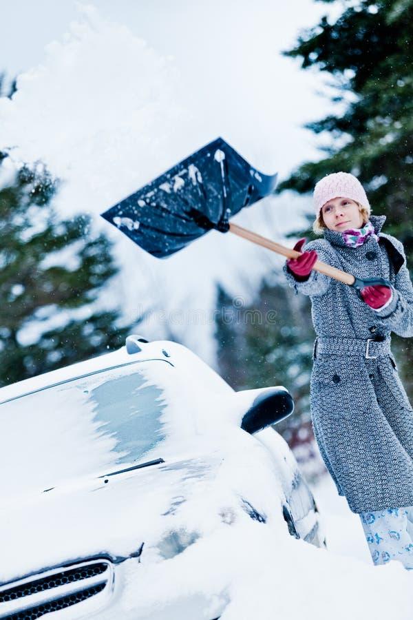 Αυτοκίνητο που κολλιέται στο χιόνι και να φτυαρίσει γυναικών στοκ φωτογραφία