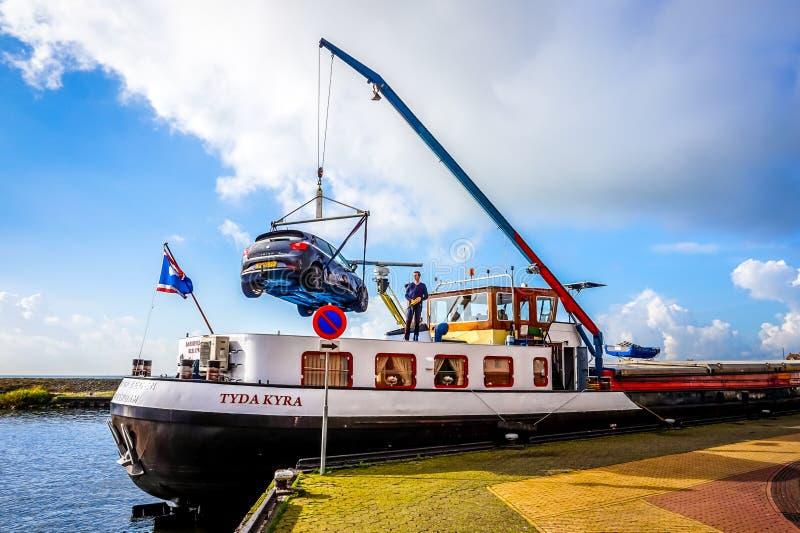 Αυτοκίνητο που ξεφορτώνεται από ένα σκάφος του Ρήνου που δένεται σε Urk στις Κάτω Χώρες στοκ εικόνες