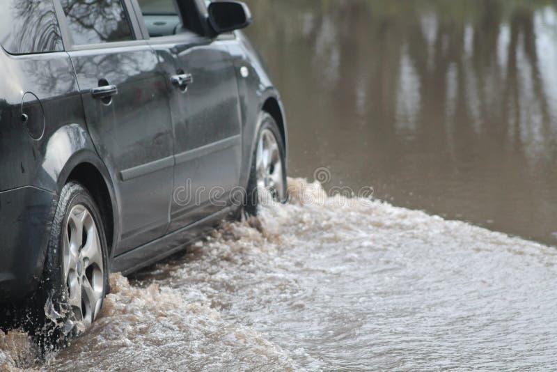 Αυτοκίνητο που περνά από την πλημμύρα στοκ φωτογραφίες