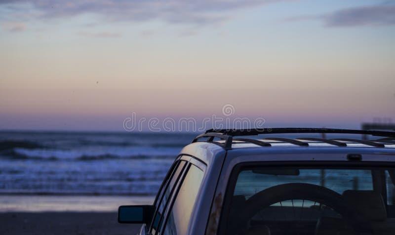 Αυτοκίνητο που σταθμεύουν στην παραλία που αντιμετωπίζει μια ανατολή στοκ φωτογραφίες