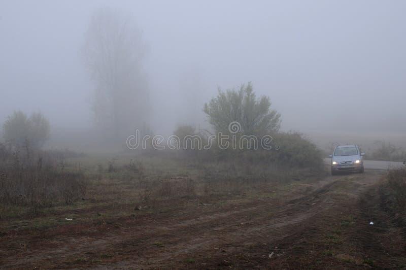 Αυτοκίνητο στο βρώμικο δρόμο την ομιχλώδη ημέρα στοκ φωτογραφίες