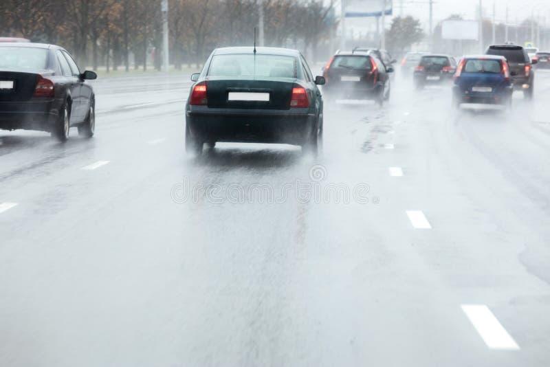 Αυτοκίνητο στο ψεκάζοντας νερό κινήσεων από τις ρόδες κατά τη διάρκεια του βροχερού weathe στοκ εικόνα