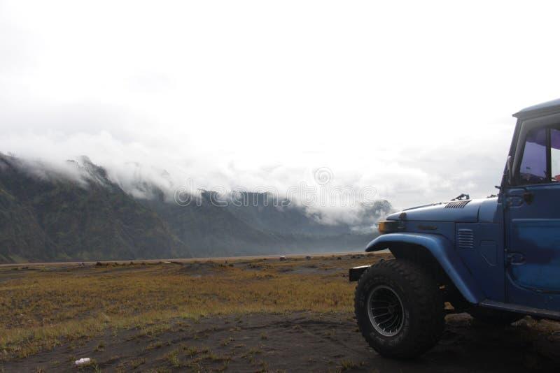 Αυτοκίνητο Land Cruiser, ομίχλη και βουνό στοκ εικόνες