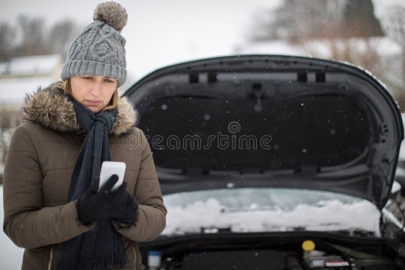Αυτοκινητιστής που αναλύει θηλυκός στο χιόνι που απαιτεί την άκρη του δρόμου Assista στοκ φωτογραφία