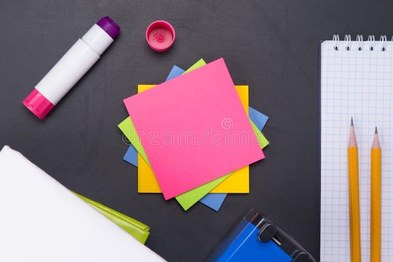 αυτοκόλλητες ετικέττες για τις σημειώσεις του ρόδινου χρώματος, σε έναν μαύρο πίνακα υπό μορφή υποβάθρου κατάρτισης στοκ εικόνα