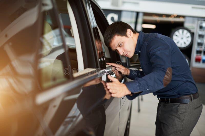 Αυτόματη επιχείρηση, πώληση αυτοκινήτων και έννοια ανθρώπων - ο ευτυχής χαμογελώντας επιχειρηματίας ή ο έμπορος στο κοστούμι πέρα στοκ εικόνα