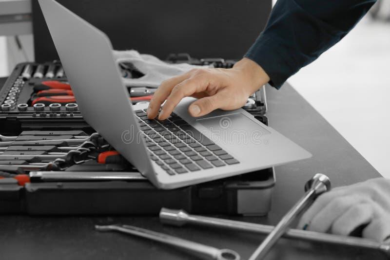 Αυτόματη μηχανική εργασία με το lap-top στο κατάστημα επισκευής αυτοκινήτων στοκ φωτογραφία με δικαίωμα ελεύθερης χρήσης