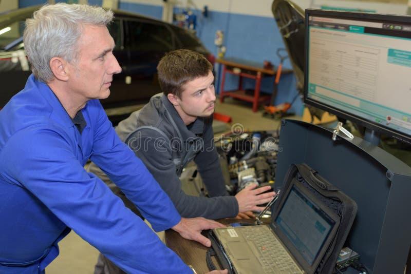 Αυτόματοι μηχανικοί δάσκαλος και εκπαιδευόμενος που εκτελούν τις δοκιμές στο μηχανικό σχολείο στοκ φωτογραφία με δικαίωμα ελεύθερης χρήσης