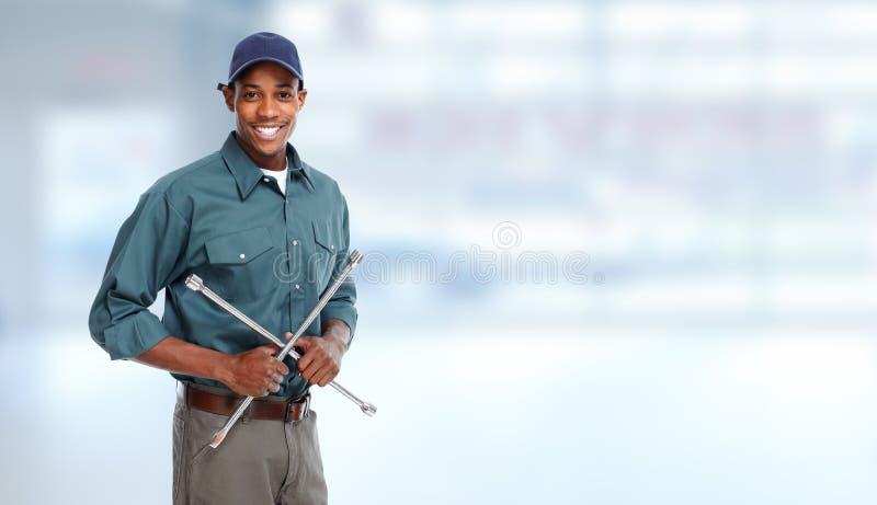 Αυτόματος μηχανικός με το γαλλικό κλειδί ροδών στο γκαράζ στοκ εικόνα με δικαίωμα ελεύθερης χρήσης