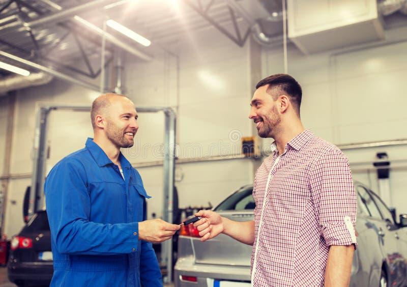 Αυτόματος μηχανικός που δίνει το κλειδί στο άτομο στο κατάστημα αυτοκινήτων στοκ φωτογραφία με δικαίωμα ελεύθερης χρήσης