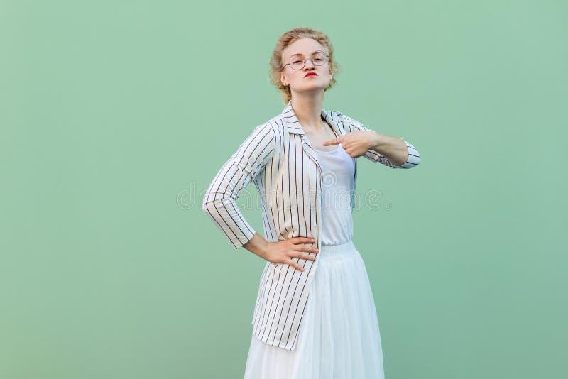 Αυτό είναι εγώ! Πορτρέτο της υπερήφανης νέας γυναίκας στην άσπρη ριγωτή μπλούζα με eyeglasses που στέκονται με το χέρι στη μέση,  στοκ εικόνες